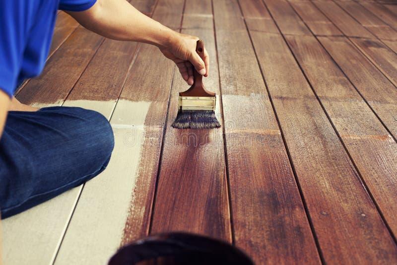 La spazzola di pittura e della mano dipinge il colore marrone sul pavimento di legno, concetto diy fotografia stock libera da diritti