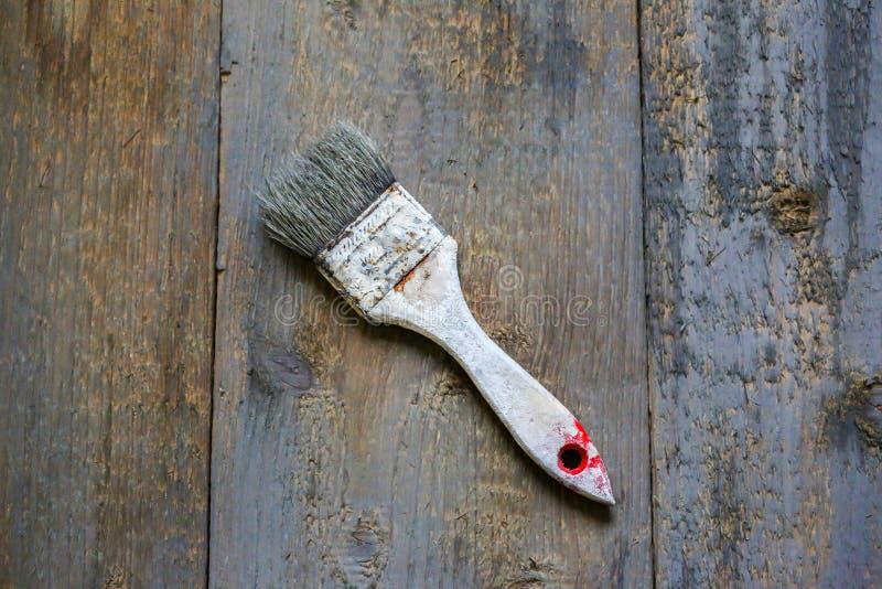La spazzola di pittura in tintura bianca della pittura sta trovandosi sui precedenti di legno Superficie d'annata grigia e marron immagini stock libere da diritti