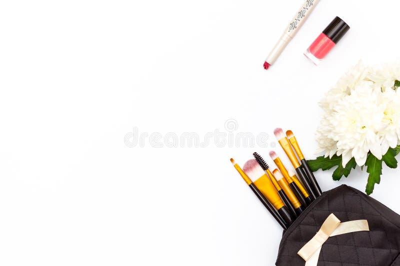 La spazzola di trucco nel trucco, il rossetto rosso, lo smalto rosa e un crisantemo fioriscono su un fondo bianco Concentrato fem immagini stock libere da diritti
