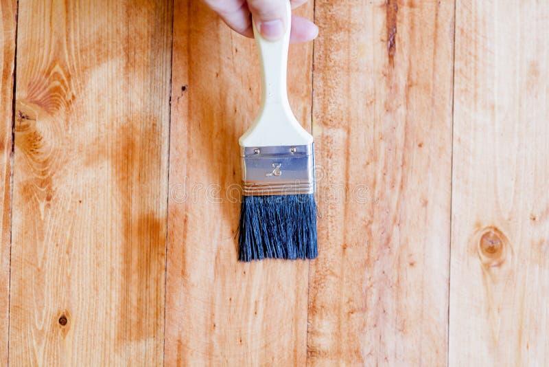 La spazzolatura per applicare la vernice dipinge su una superficie di legno fotografia stock