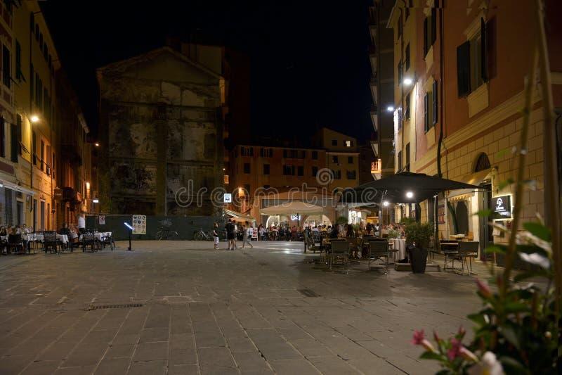 LA SPEZIA, ITALIA, EL 4 DE JULIO DE 2019: Plaza Sant Agustín en la noche con las barras y los restaurantes de la calle en la ciud imagen de archivo libre de regalías