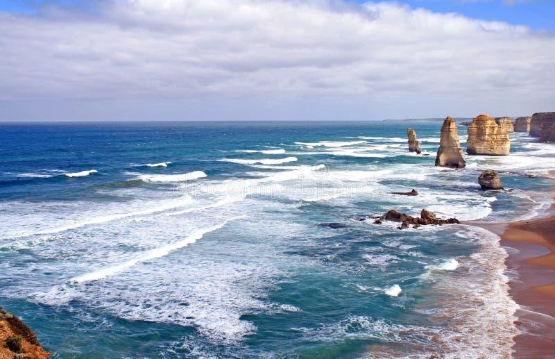La spiaggia australiana con spuma e 12 apostoli le formazioni rocciose fotografia stock