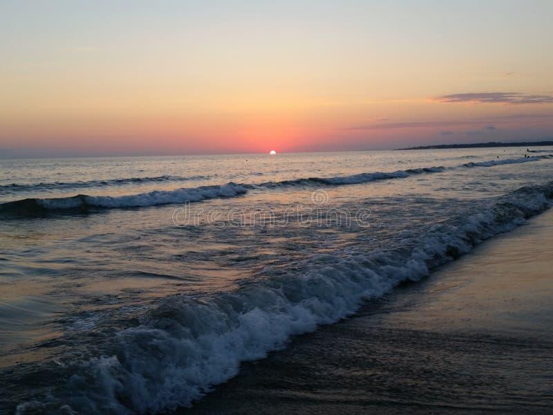 La spiaggia del tramonto ondeggia skay arancio fotografia stock