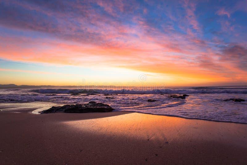 La spiaggia oscilla il paesaggio di colore di alba dell'acqua fotografia stock