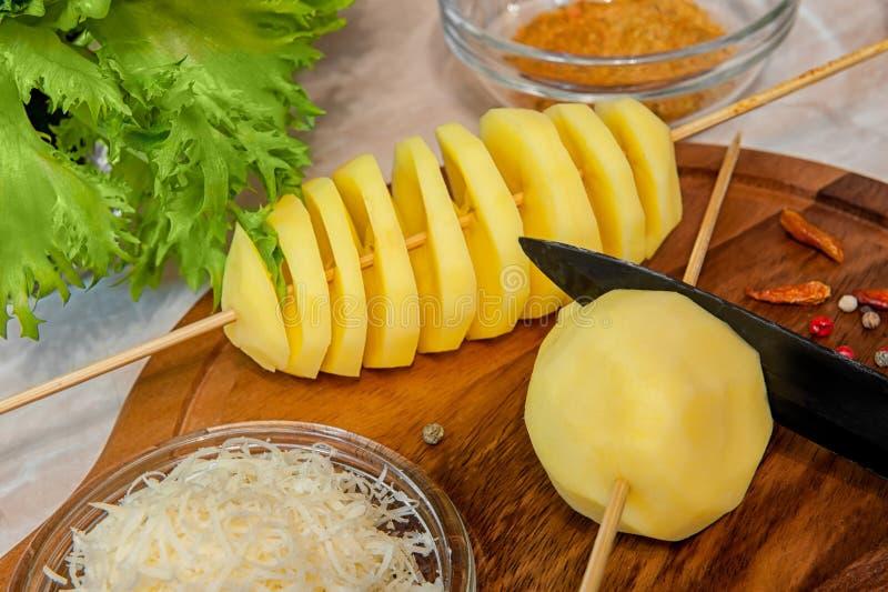La spirale della patata cruda ha tagliato gli spiedi con formaggio, aglio, le erbe provanskiy e l'insalata verde immagini stock libere da diritti