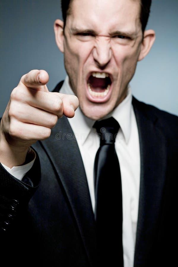 La sporgenza arrabbiata indica la barretta all'impiegato e grida. fotografia stock libera da diritti