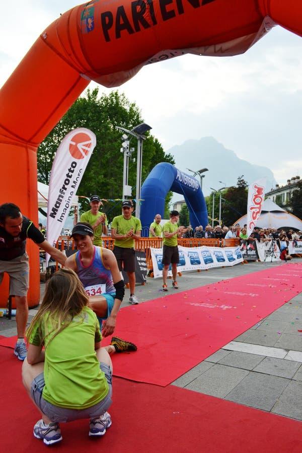 """La sportive est arrivée à la finition """"ville de Lecco - de l'événement courant de marathon de montagne de Resegone """" photo libre de droits"""