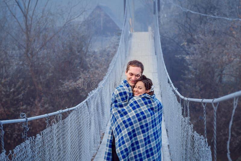 La sposa adorabile e lo sposo wripped in coperta abbraccia morbidamente sul ponte di legno Luna di miele alle montagne immagine stock libera da diritti