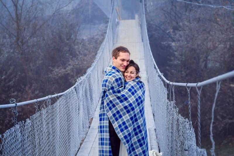 La sposa adorabile e lo sposo wripped in coperta abbraccia morbidamente sul ponte di legno Luna di miele alle montagne fotografie stock libere da diritti