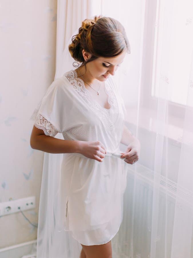 La sposa adorabile nell'abito di seta che sta vicino alla finestra immagini stock