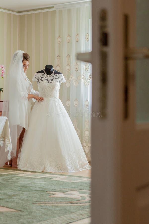 La sposa affascinante con le damigelle d'onore sta vicino al vestito da sposa Preparazione nuziale di mattina di nozze fotografie stock libere da diritti