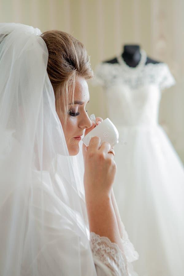 La sposa affascinante con le damigelle d'onore sta vicino al vestito da sposa Preparazione nuziale di mattina di nozze fotografia stock
