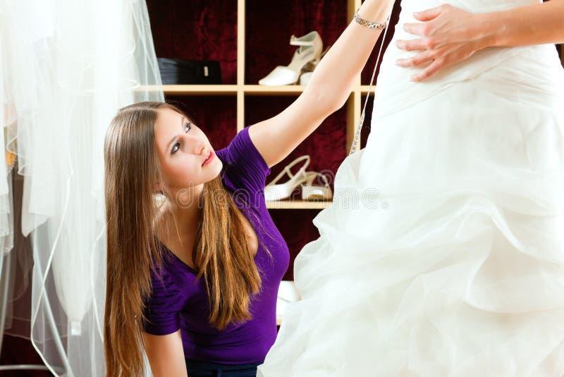 La sposa ai vestiti acquista per i vestiti da cerimonia nuziale fotografia stock libera da diritti