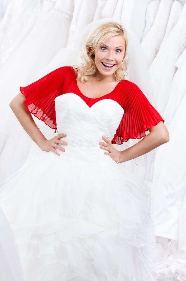 La sposa ammira il suo vestito da cerimonia nuziale fotografia stock libera da diritti