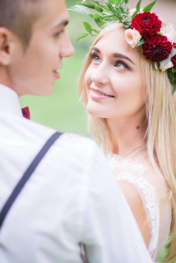 La sposa ammira lo sposo attraente mentre sta prima di lui immagini stock libere da diritti