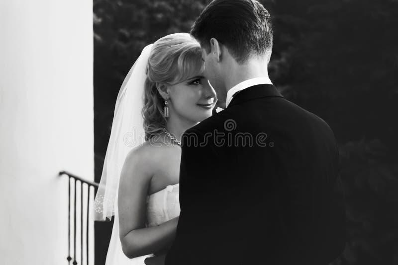 La sposa ammira uno sposo che pende a lui sul balcone fotografia stock libera da diritti