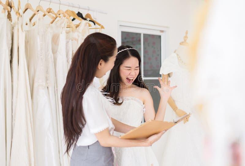 La sposa asiatica della giovane donna ha colpito la fattura con costo, progettista della donna che procede all'adeguamento in stu fotografia stock libera da diritti