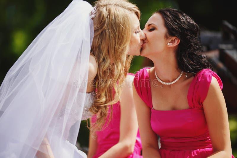 La sposa bacia le labbra di una damigella d'onore in vestito rosa fotografia stock