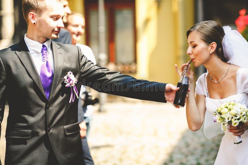 La sposa beve la soda da una bottiglia tenuta dal groomsman fotografie stock