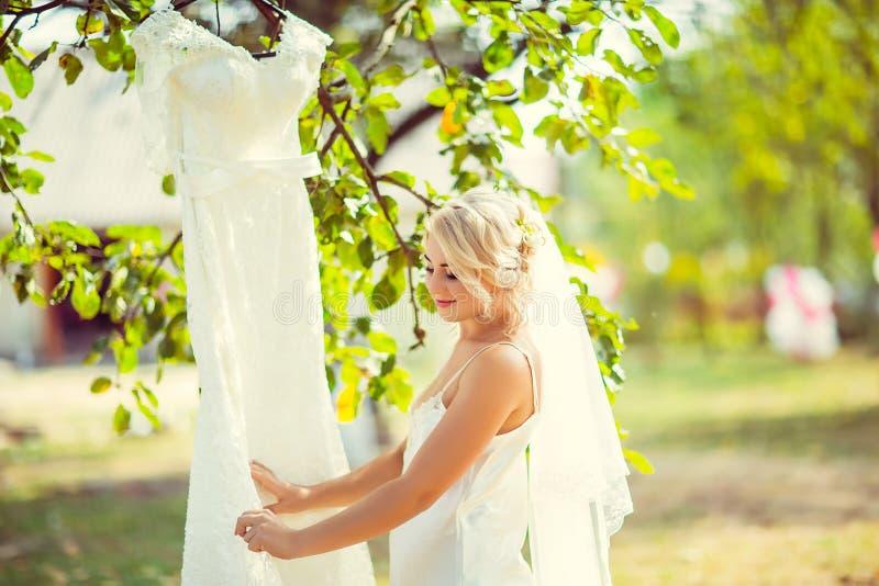 La sposa bionda esamina le sue nozze, appendendo su un albero e su un giardino, la mattina della sposa, fuoco selettivo fotografia stock libera da diritti