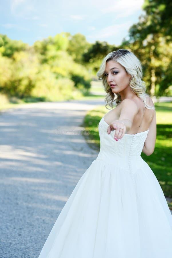 La sposa bionda mi segue che cammino giù il passaggio pedonale del giardino fotografia stock