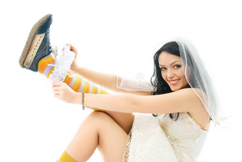 La sposa che porta i pattini di sport mette sopra una giarrettiera immagine stock