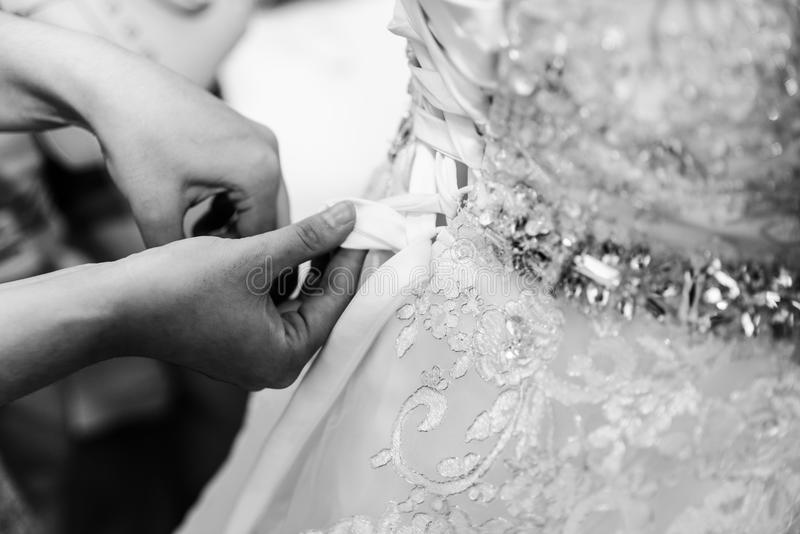 La sposa che sta portando un vestito da sposa immagine stock