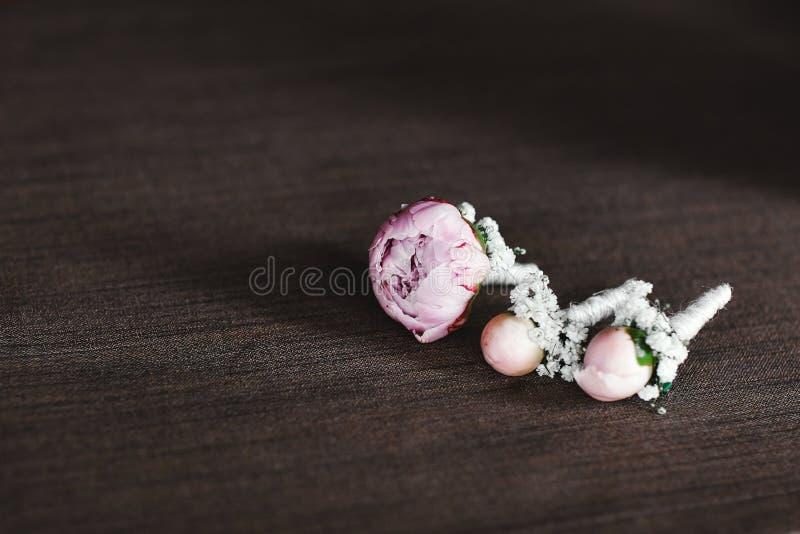 La sposa che tengono a disposizione primo piano i fiori dell'occhiello dello sposo con le rose bianche e verde e pianta immagine stock libera da diritti