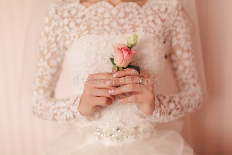 La sposa che tengono a disposizione primo piano i fiori dell'occhiello dello sposo con le rose bianche e verde e pianta fotografia stock