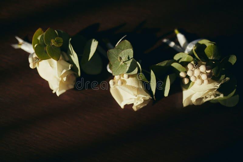 La sposa che tengono a disposizione primo piano i fiori dell'occhiello dello sposo con le rose bianche e verde e pianta immagini stock libere da diritti