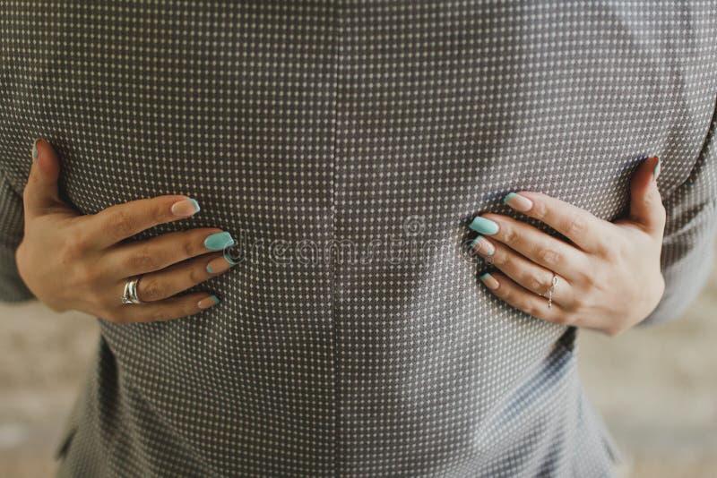 La sposa con le unghie blu-chiaro tiffany del manicure di colore sta abbracciando lo sposo in vestito a quadretti grigio immagini stock