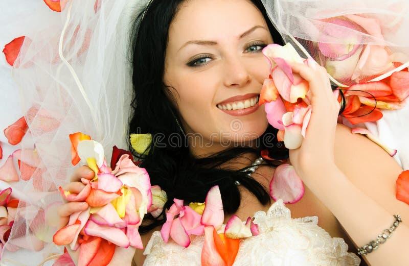 La sposa del Brunette sulla base coperta di rosa va fotografie stock