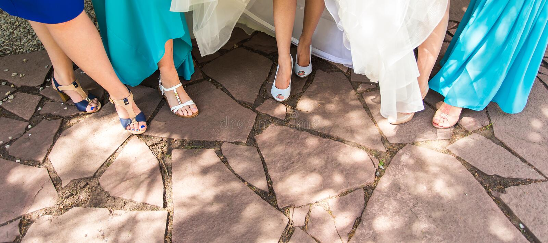La sposa e le damigelle d'onore ostentano le loro scarpe a nozze fotografie stock libere da diritti