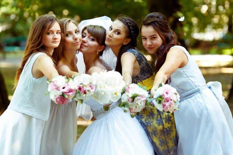 La sposa e le damigelle d'onore raggiungono le mani con i mazzi al cineoperatore immagini stock