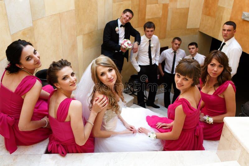 La sposa e le damigelle d'onore si siedono sulle scale bianche mentre sposo ed il gr fotografia stock