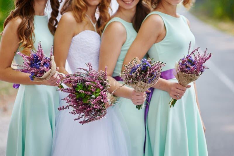 La sposa e le damigelle d'onore stanno mostrando i bei fiori sulle loro mani fotografia stock libera da diritti