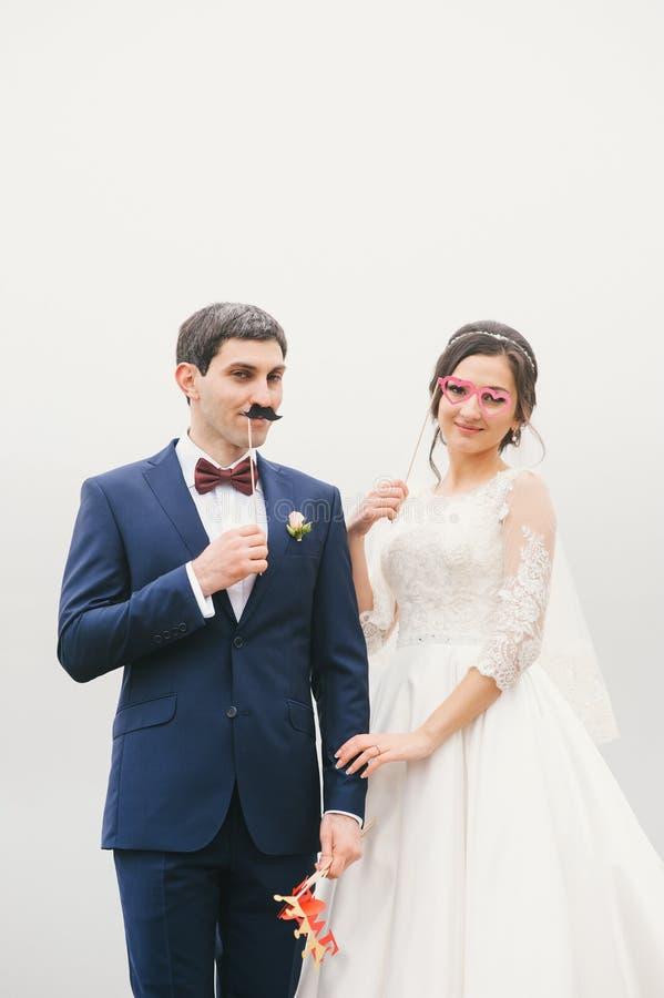 La sposa e lo sposo allegati al fronte incartano i baffi, vetri fotografie stock libere da diritti