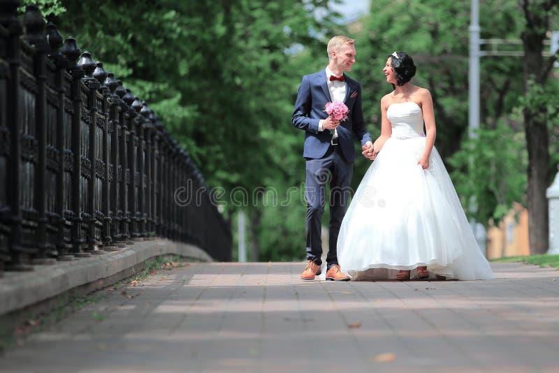 La sposa e lo sposo camminano in un parco della città immagine stock