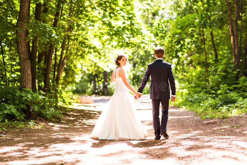 La sposa e lo sposo che si allontanano di estate parcheggiano all'aperto fotografia stock libera da diritti