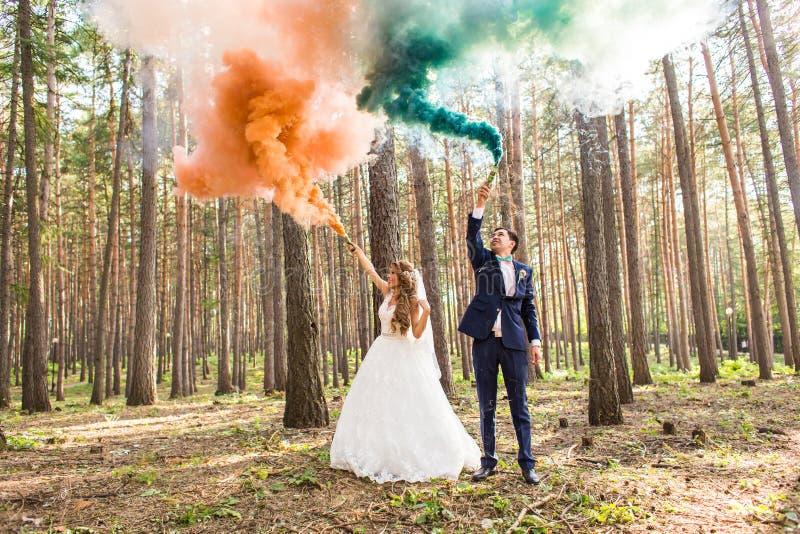 La sposa e lo sposo con le bombe fumogene sui precedenti degli alberi fotografia stock libera da diritti