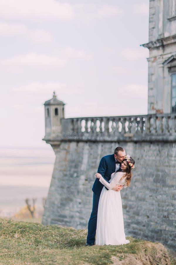 La sposa e lo sposo della persona appena sposata baciano vicino alla bella parete barrocco della fortezza Vista magnifica del cie immagini stock