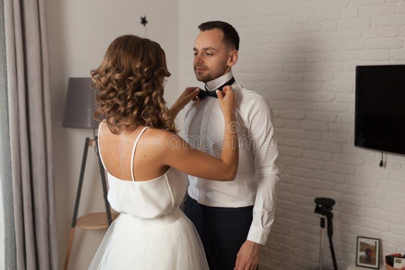 La sposa e lo sposo di mattina all'hotel su un giorno delle nozze Vestendo una donna neo-sposata delle coppie contribuisca a ripa immagini stock libere da diritti
