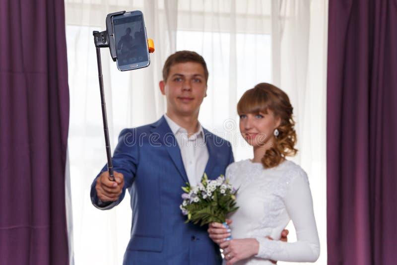 la sposa e lo sposo fanno il selfie Fuoco sul telefono fotografie stock libere da diritti