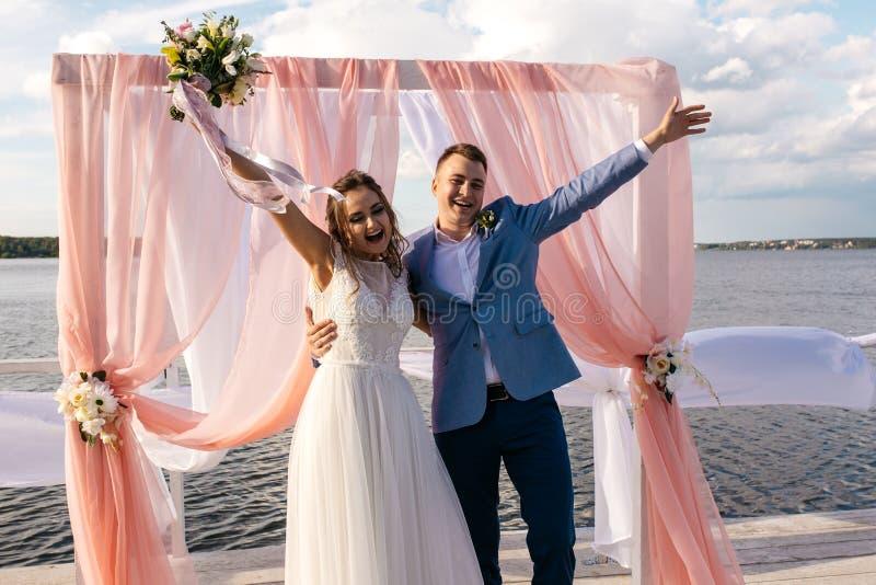 La sposa e lo sposo felici stanno sul pilastro sotto l'arco di nozze immagini stock libere da diritti