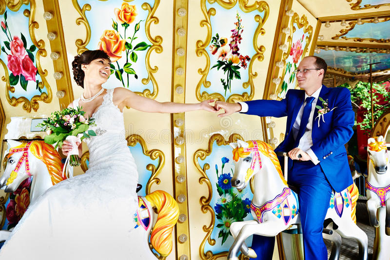 La sposa e lo sposo felici sulla fiera di divertimento dei cavalli dei giocattoli a nozze camminano fotografia stock