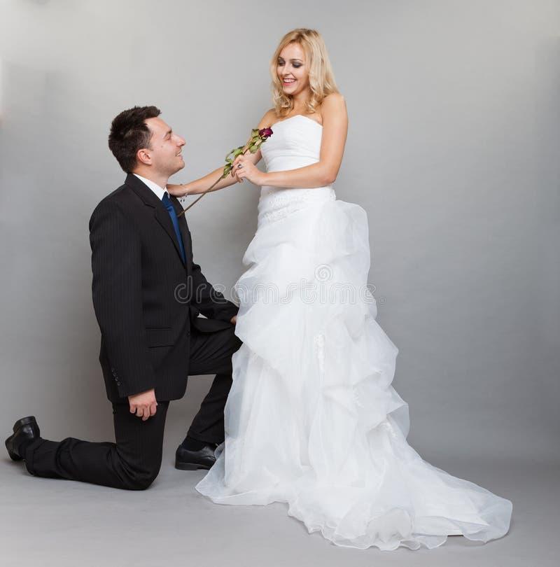 La sposa e lo sposo romantici della coppia sposata con sono aumentato immagini stock libere da diritti