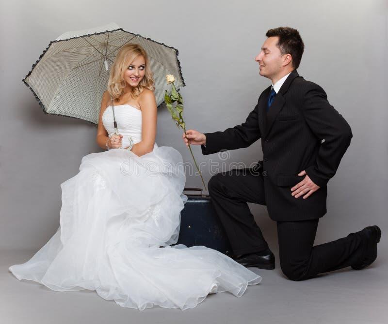 La sposa e lo sposo romantici della coppia sposata con sono aumentato fotografia stock libera da diritti
