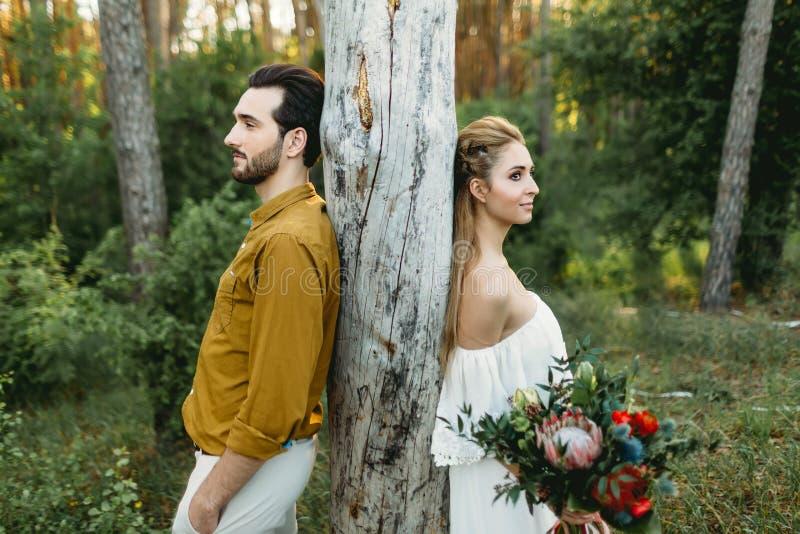 La sposa e lo sposo si appoggiano l'albero dai lati differenti Le persone appena sposate stanno camminando nel materiale illustra immagini stock