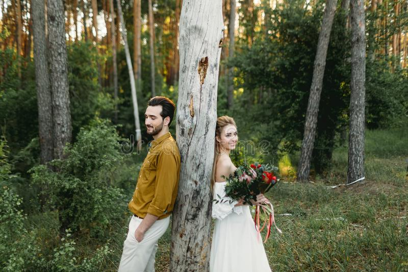 La sposa e lo sposo si appoggiano l'albero dai lati differenti Le persone appena sposate stanno camminando nel materiale illustra fotografia stock