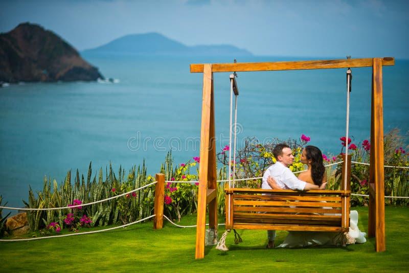 La sposa e lo sposo si siedono su un'oscillazione fotografia stock libera da diritti